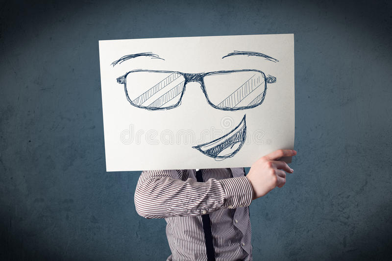Businessman holding a paper with smiley face in front of his head. Young businessman holding a paper with smiley face in front of his head royalty free stock image