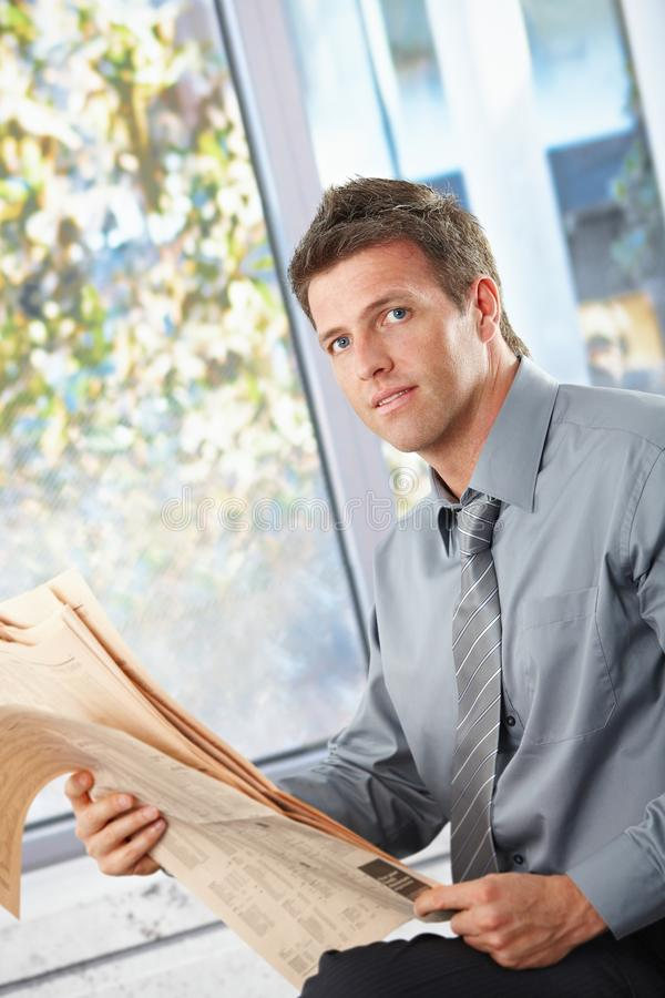 Download Businessman Holding Papers Looking At Camera Stock Photo - Image: 13140460