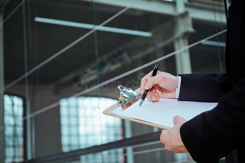 Businessman holding pen and clipboard stock images