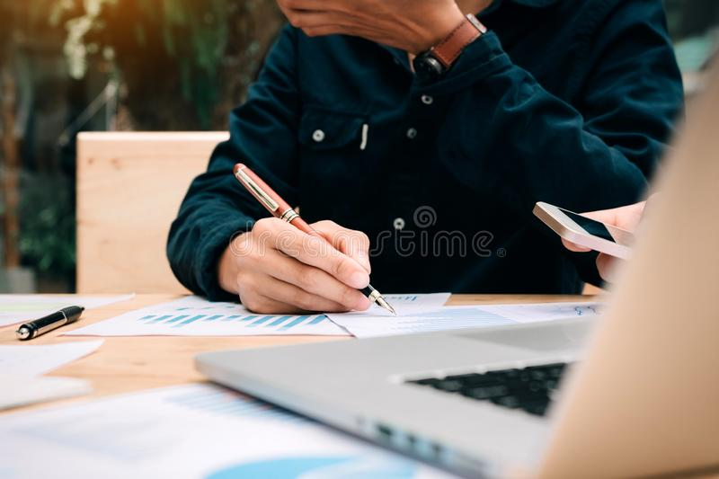 Businessman holding pen and pointing paper chart summary analyzing annual business report with using laptop at room office desk.  royalty free stock photo