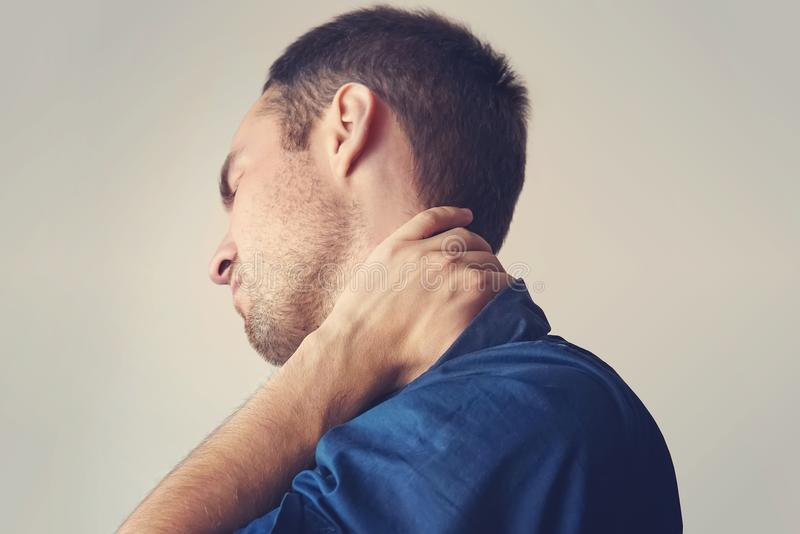 Businessman holding a phone and her neck with pain. Young guy holding his neck. a sore neck. chondrosis. the concept of health. fracture of the cervical spine stock images