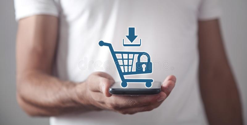 Businessman holding a phone with a shopping cart. Shopping security. Online shopping royalty free stock photos