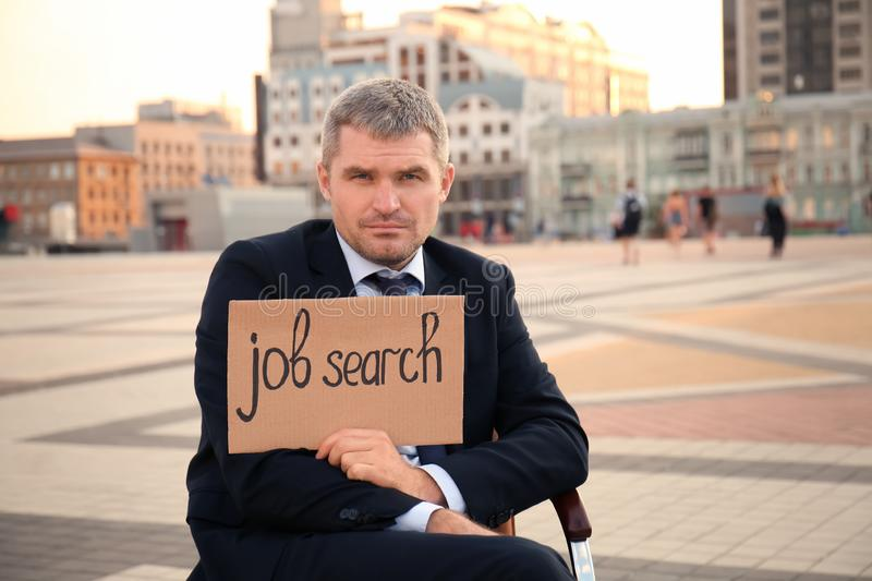 Businessman holding piece of cardboard with text JOB SEARCH while sitting in office armchair outdoors royalty free stock photography