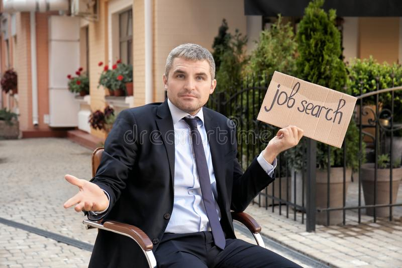 Businessman holding piece of cardboard with text JOB SEARCH while sitting in office armchair outdoors royalty free stock images