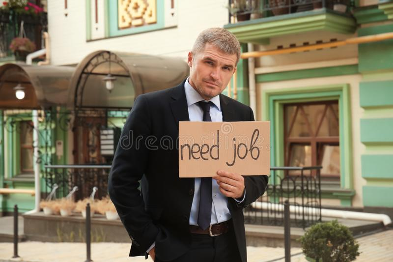 Businessman holding piece of cardboard with text NEED JOB outdoors royalty free stock photo