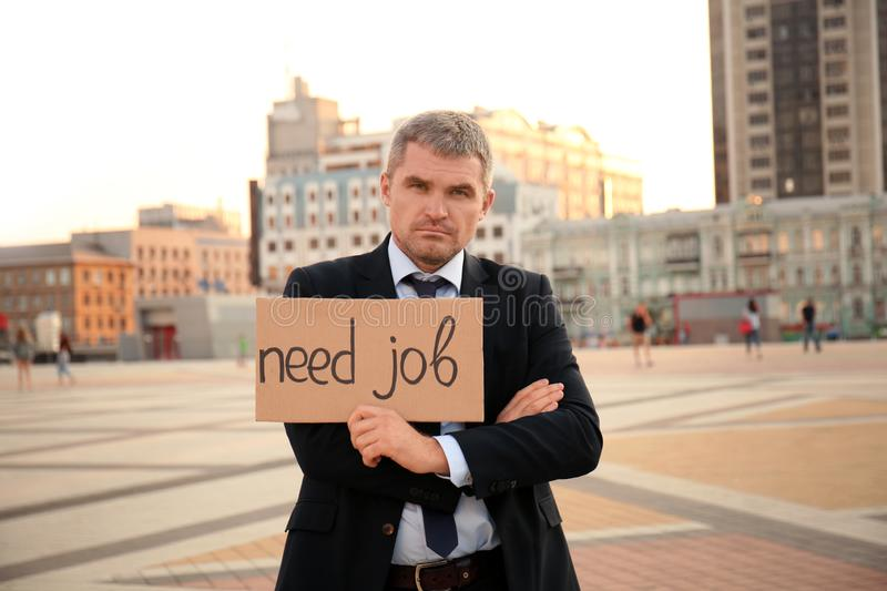 Businessman holding piece of cardboard with text NEED JOB outdoors stock images