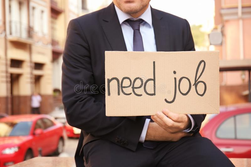 Businessman holding piece of cardboard with text NEED JOB outdoors royalty free stock image