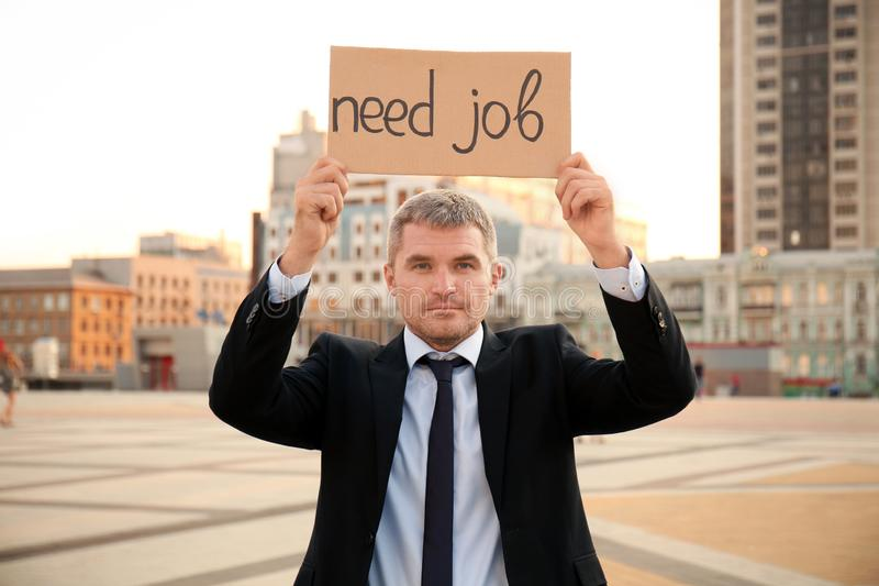 Businessman holding piece of cardboard with text NEED JOB outdoors stock photography
