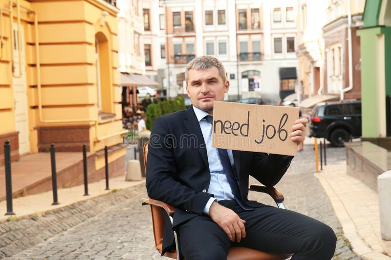 Businessman holding piece of cardboard with text NEED JOB while sitting in office armchair outdoors royalty free stock photos