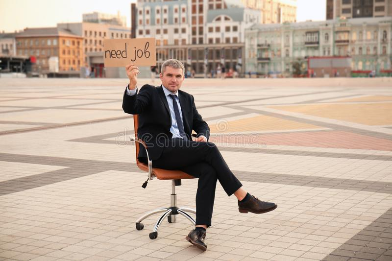 Businessman holding piece of cardboard with text NEED JOB while sitting in office armchair outdoors royalty free stock image