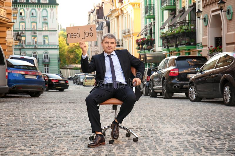 Businessman holding piece of cardboard with text NEED JOB while sitting in office armchair outdoors stock photography