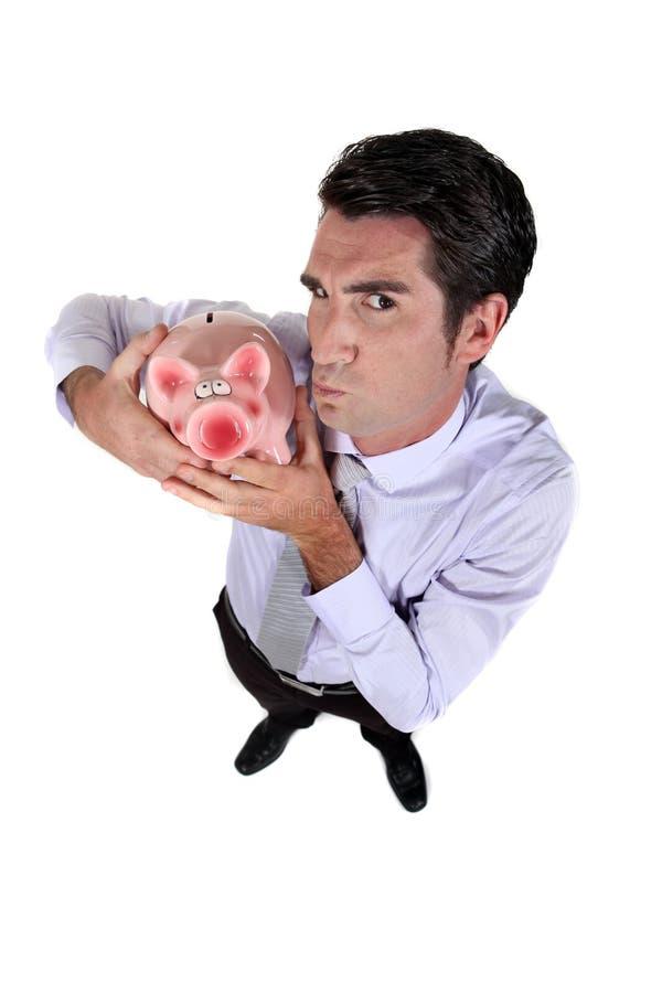 Businessman holding piggy-bank royalty free stock photos