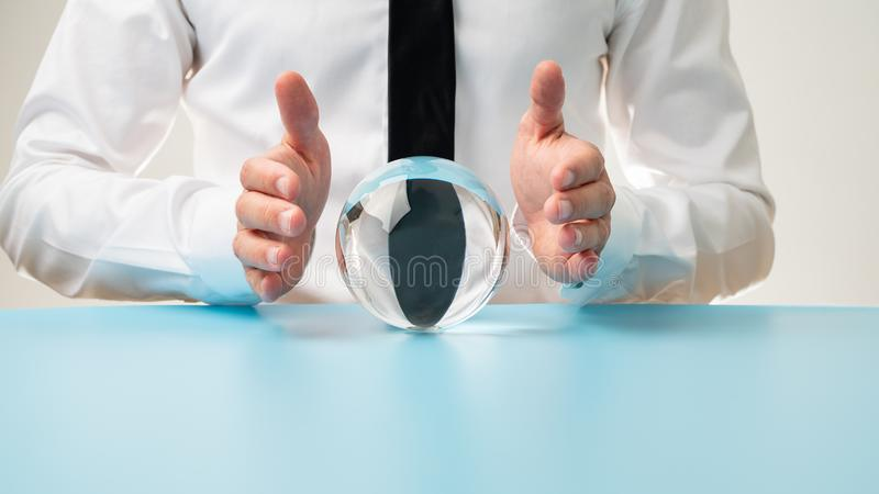 Businessman holding protective hands over a crystal ball. In a conceptual image stock photo