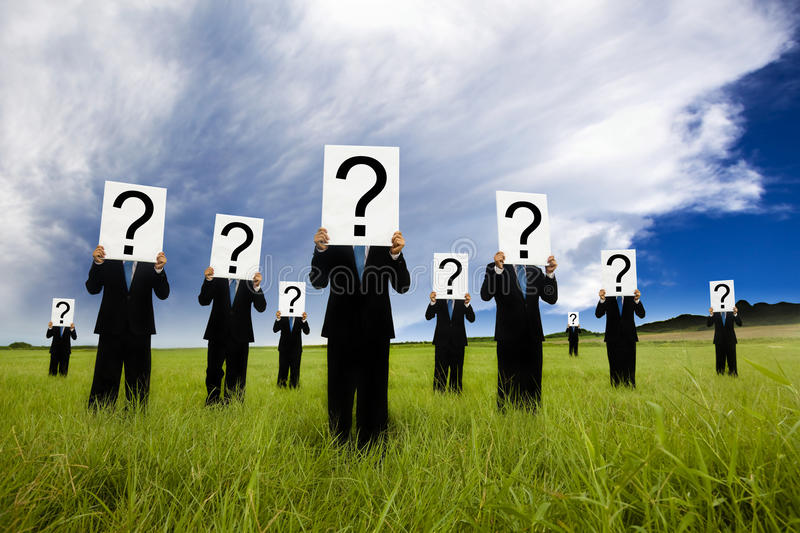 Businessman holding question mark. Group of businessman in black suit and holding question mark symbol royalty free stock photo