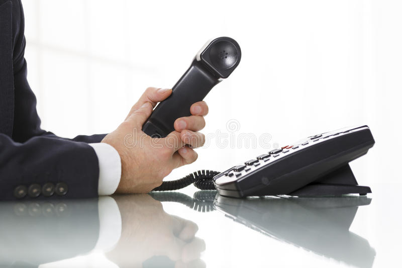 Businessman holding the receiver of a black landline telephone. Businessman with dark gray suit holding the receiver of a black landline telephone. Close up of royalty free stock image