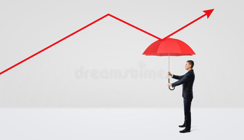 A businessman holding a red open umbrella right under a red statistic arrow pointing upwards. Avoiding losses. Measures against failure. Accounting tips stock photo