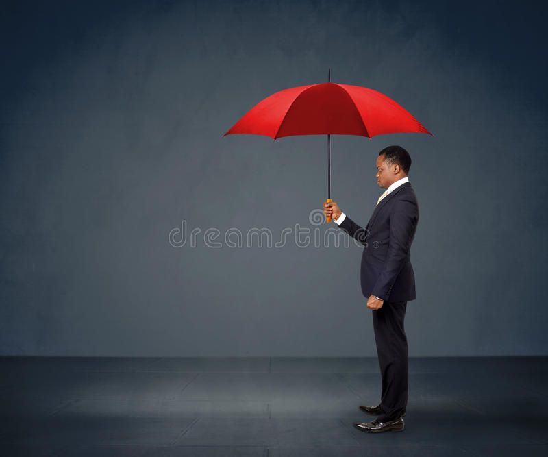 Businessman holding red umbrella. African American businessman holding a red umbrella stock photos