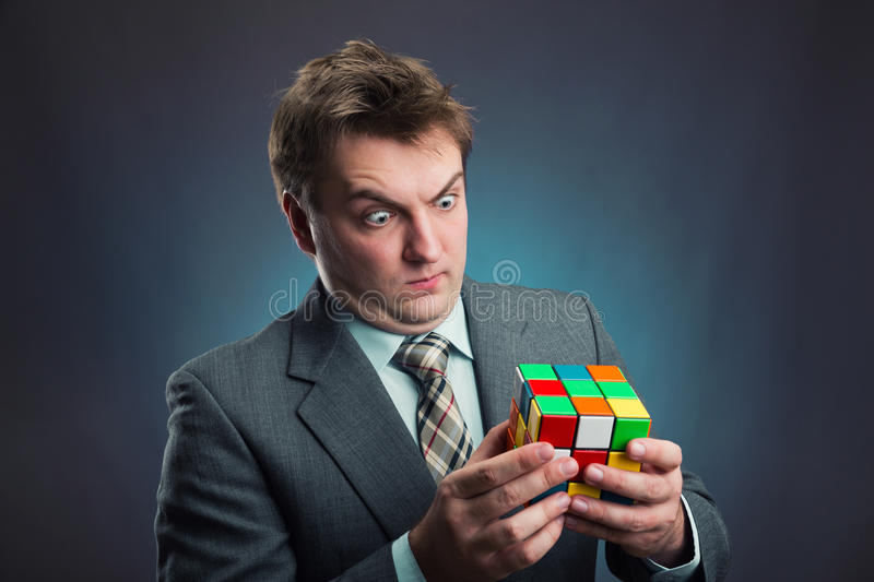 Businessman holding rubik cube in his hands. Businessman looking at rubik cube in his hands royalty free stock photo