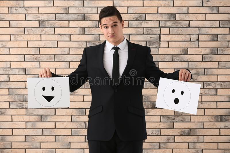 Businessman holding sheets of paper with drawn emoticons against brick wall royalty free stock photos