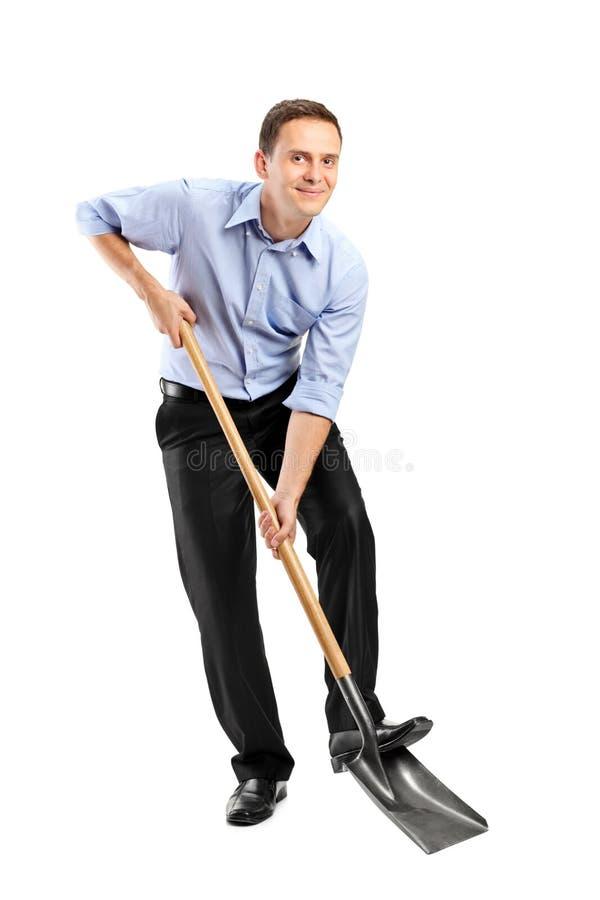 Businessman holding a shovel royalty free stock photography