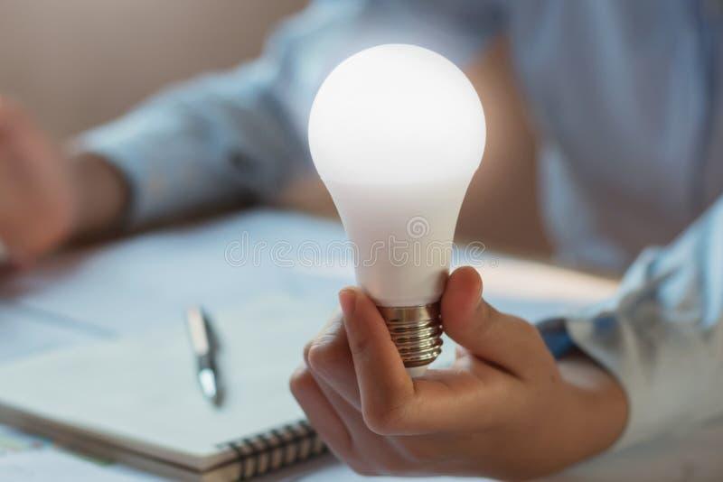 Businessman holding show led bulb. concept saving power. Energy stock photography