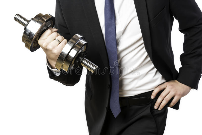Businessman holding silver dumbbell. Businessman in black suit holding a silver dumbbell in the right hand stock image