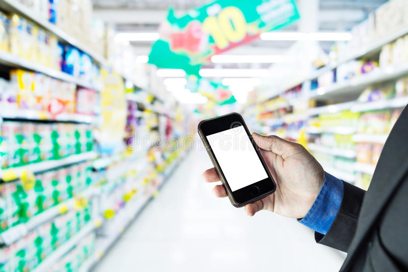 Businessman holding smart phone, in supermarket aisle background stock photography