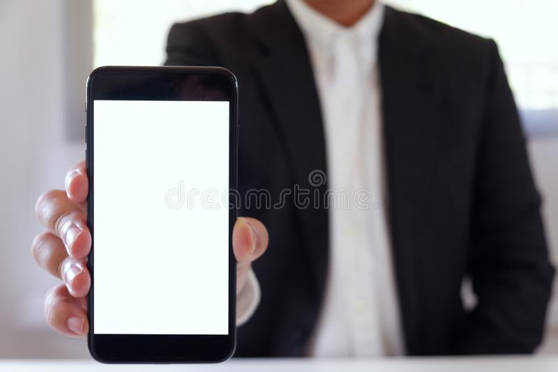 Businessman holding smartphone forward empty white screen for your text or picture. stock photography