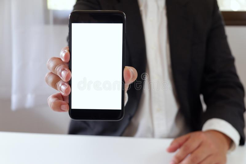 Businessman holding smartphone forward empty white screen for your text or picture stock images