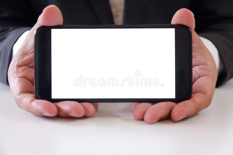 Businessman holding smartphone forward empty white screen for your text or picture stock image