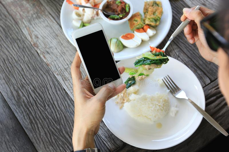 Businessman holding smartphone and having lunch in restaurant.  royalty free stock images
