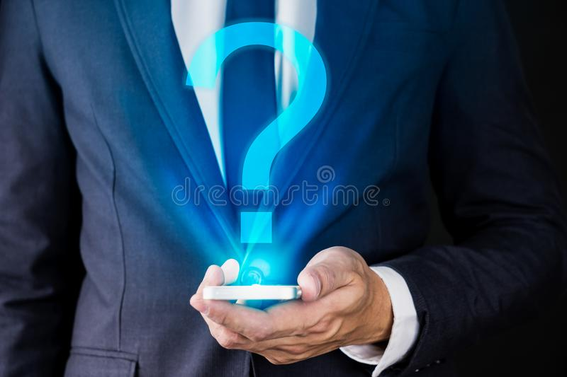 Businessman Holding Smartphone with Question mask on Hologram te royalty free stock images