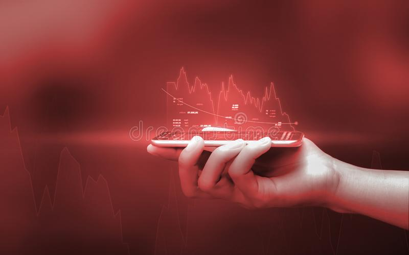 Businessman holding smartphone and showing holographic graphs and stock market statistics lost profits. Concept of growth planning. And business strategy stock image