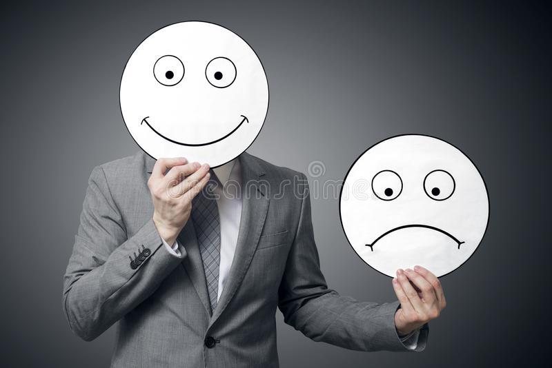 Businessman holding smile and sad mask. Conceptual image of a man changing his mood from bad to good. Business concept stock photo