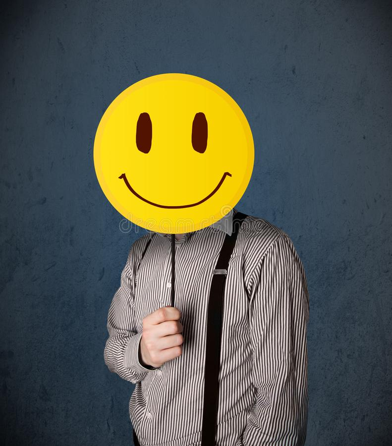 Businessman holding a smiley face emoticon. Businessman holding a yellow smiley face emoticon in front of his head royalty free stock photography