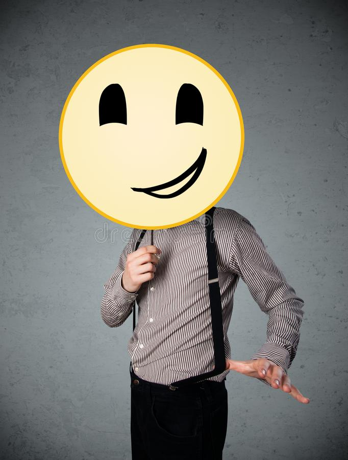 Businessman holding a smiley face emoticon. Businessman holding a yellow smiley face emoticon in front of his head royalty free stock images