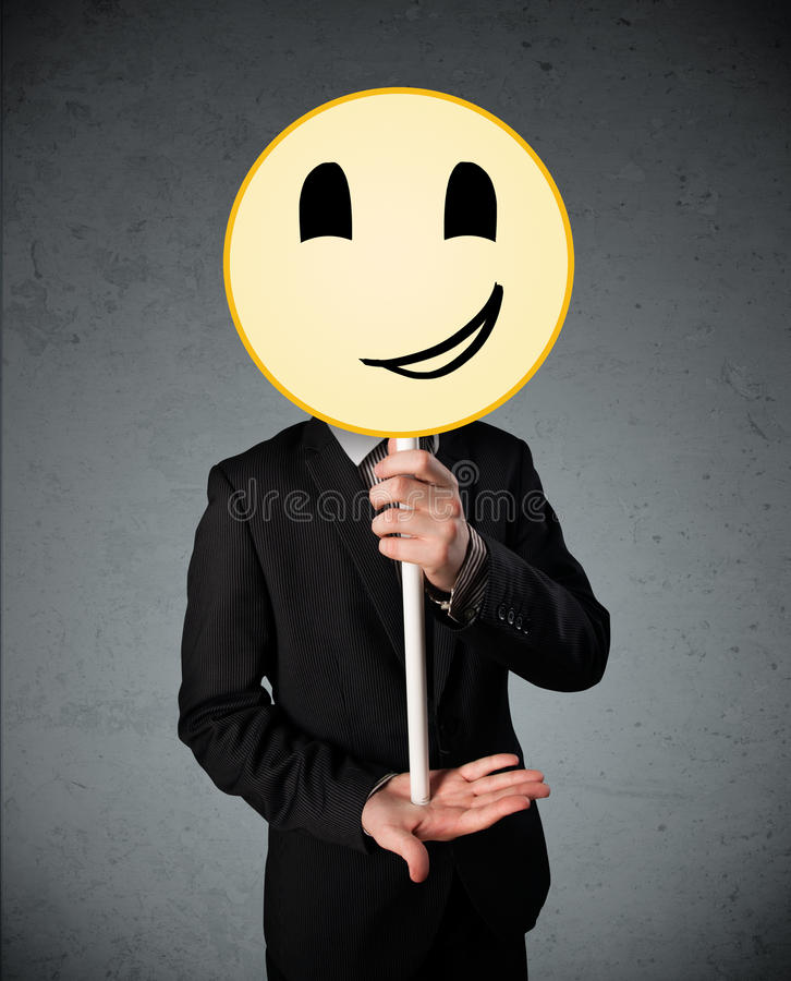 Businessman holding a smiley face emoticon. Businessman holding a yellow smiley face emoticon in front of his head stock photos