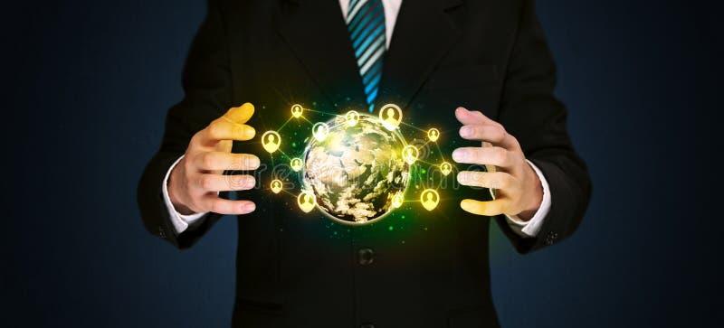 Businessman holding a social media globe. Businessman holding a shining globe with social media connection royalty free stock photography
