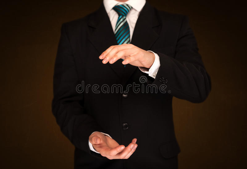 Businessman holding something. In front of his body stock photos