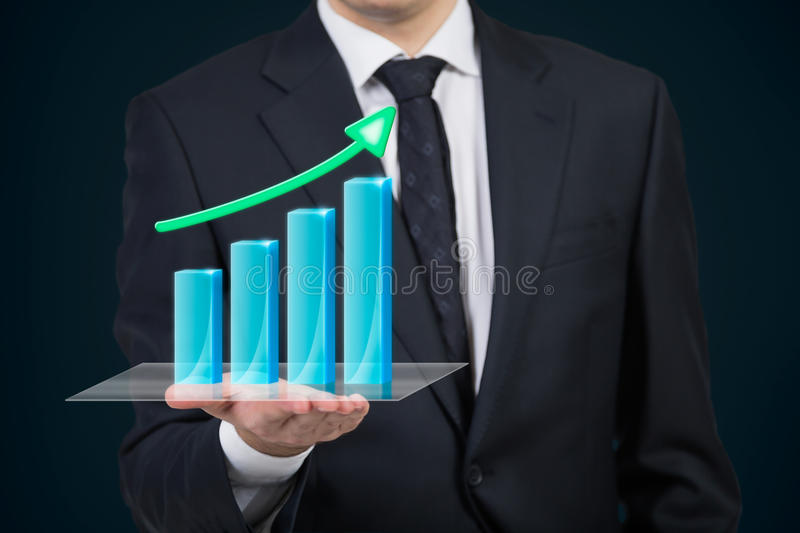 Businessman holding stock graph. Businessman holding stock chart with arrow royalty free stock image