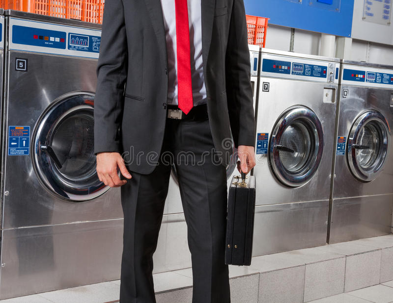Businessman Holding Suitcase In Laundry stock photo
