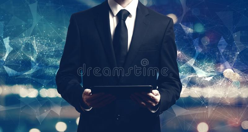 Businessman holding a tablet. Computer on night city background royalty free stock photos