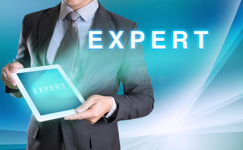 businessman holding tablet with EXPERT word with abstract background for Business royalty free stock photos