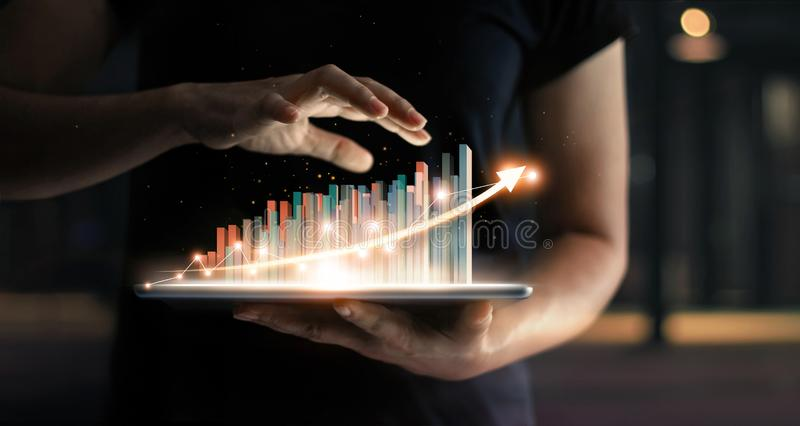 Businessman holding tablet of growing virtual statistic hologram royalty free stock images