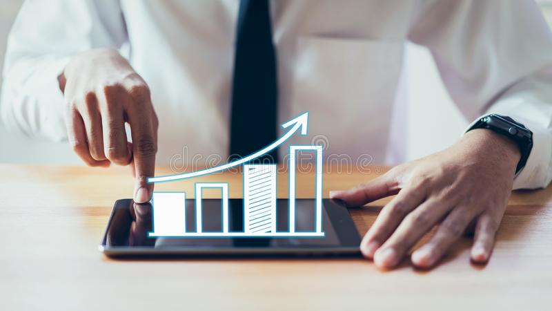 Businessman holding tablet and have a chart showing business growth. royalty free stock images