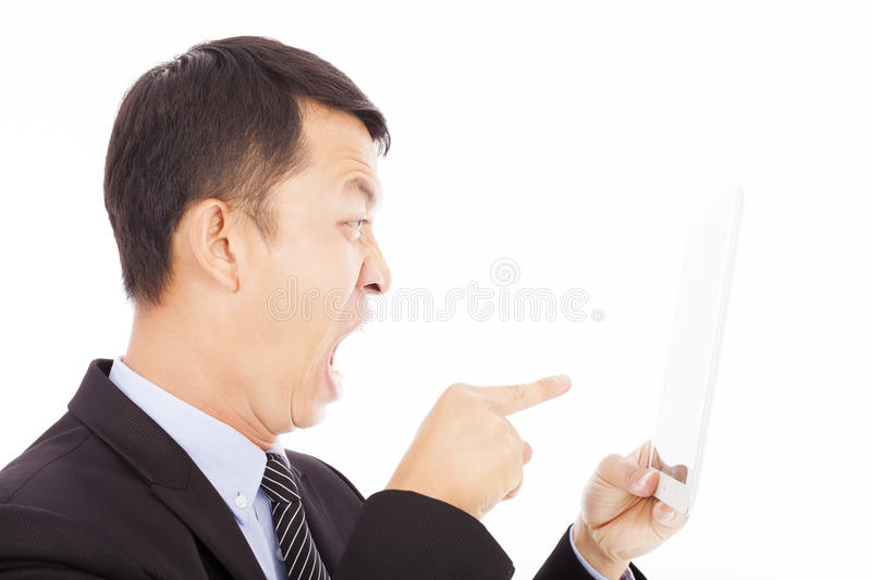 Businessman holding a tablet or ipad and screaming to point it stock photos
