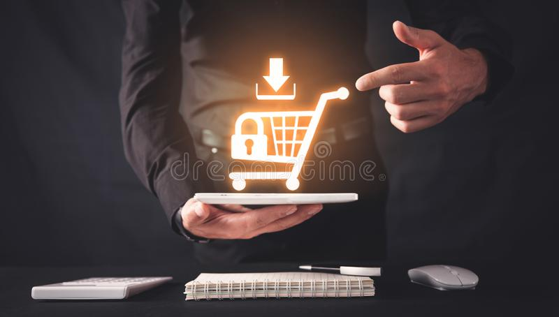 Businessman holding a tablet with a shopping cart. Shopping security. Online shopping royalty free stock photography