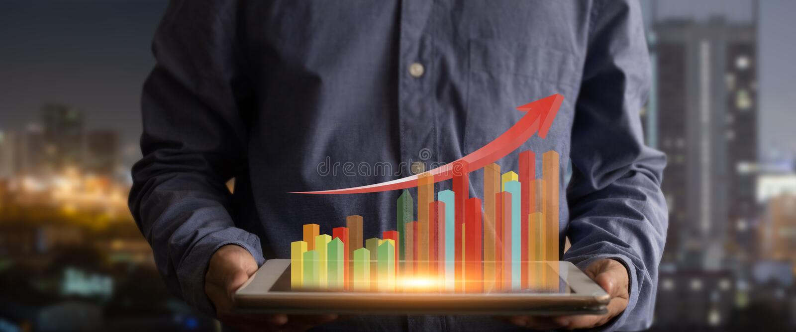 Businessman holding tablet and showing graph of growing hologram royalty free stock image