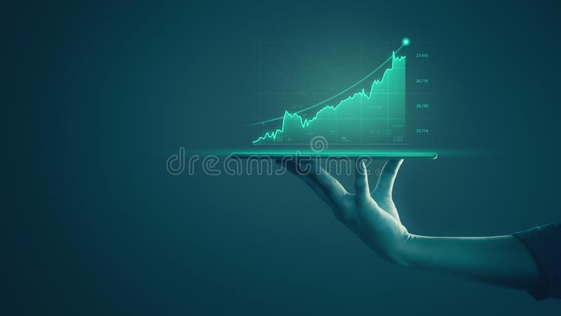 Businessman holding tablet and showing holographic graphs and stock market statistics gain profits. Concept of growth planning and stock photography