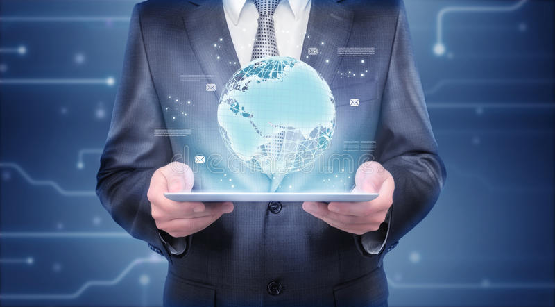 Businessman holding tablet which is showing hologram of the Earth. Businessman holding a tablet which is showing a hologram of the Earth. Digital imaging of the royalty free stock photos